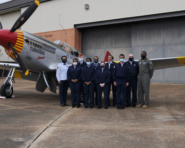 """Columbus High School Junior Reserve Officers' Training Corps (JROTC) pose for a photo beside the Commemorative Air Force Red Tail Squadron's P-51C Mustang, named """"Tuskegee Airmen"""" on Feb. 10, 2020, at Columbus Air Force Base, Miss. The CAF visited Columbus AFB from Feb. 10-12 to help commemorate the Tuskegee Airmen. (U.S. Air Force photo by Mary Crump)"""