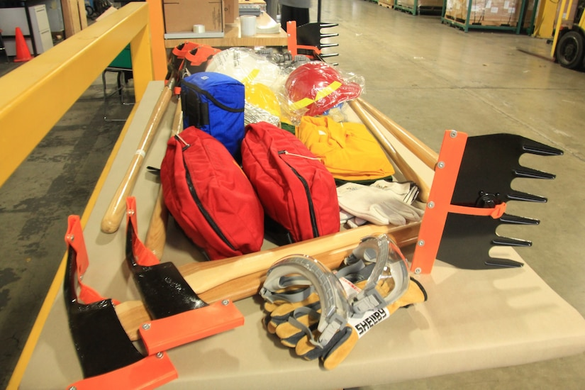 A number of heavy-duty picks, racks, work gloves, helmets, goggles and equipment in nylon bags sit on a table.