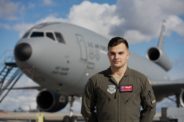 Airman poses in front of an aircraft