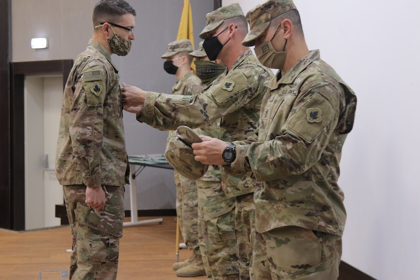 Sergeant Major Alex Young pins Joseph Nowak to Staff Sergeant at Joint Training Center in Jordan on January 28 2021. Staff Sgt. Nowak provides mobility support and accountability to all units to facilitate personnel and equipment onward movement and integration within Jordan.
