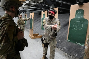 A 119th Security Forces Squadron shooting instructor demonstrates how to hold a pistol for accuracy near targets at the Tech. Sgt. Trent O`Brien, a 119th Security Forces Squadron instructor demonstrate shooting positions during M9 weapons training at the Fargo Regional Law Enforcement Training Center Range, Fargo, N.D., Feb. 4, 2021.
