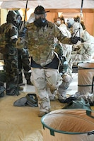 A 119th Wing military member wears a gas mask and a protective suit as he practices washing off simulated material from a chemical, biological, radiological or nuclear attack.