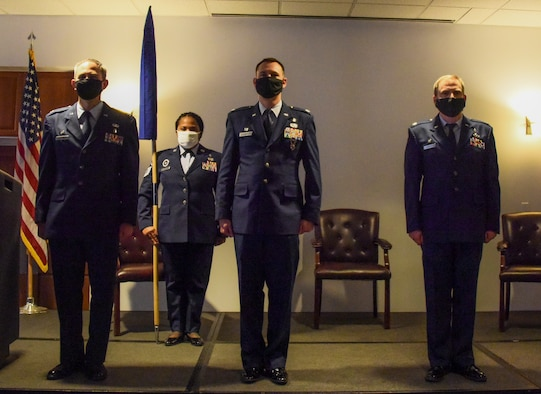 Four service members stand at attention.