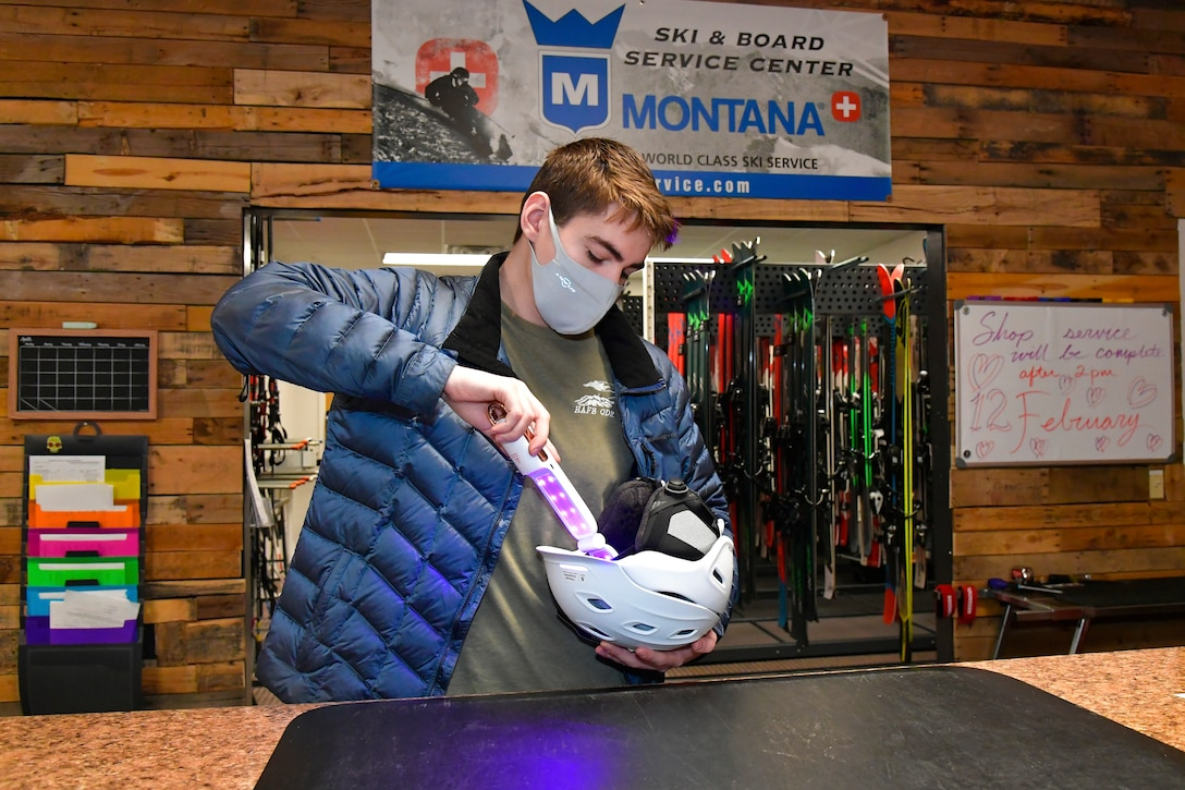Austin Lynnville, outdoor recreation clerk and ski technician, uses a ultra violet wand to sterilize ski equipment.