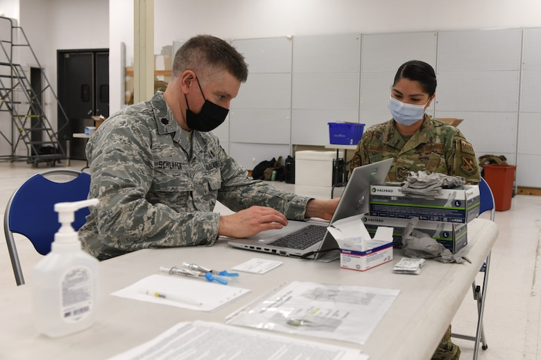 Air Force colonel administers COVID-19 vaccine to female Airman.