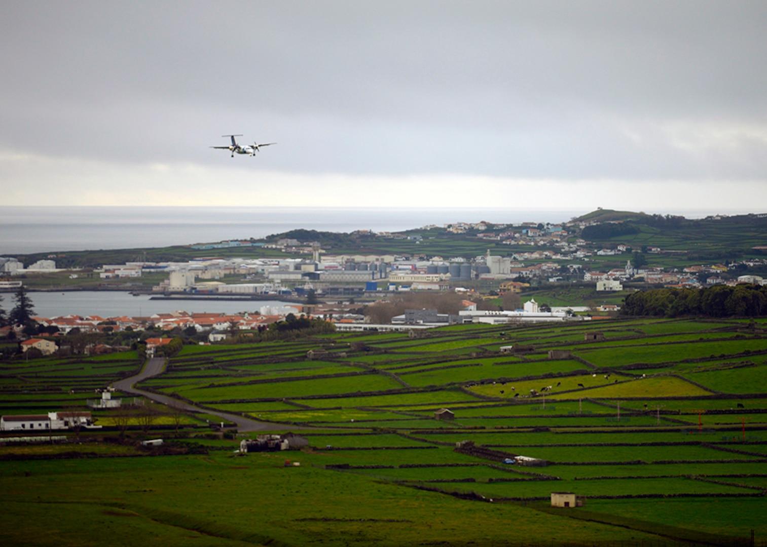 A plane lands in an oceanside village.