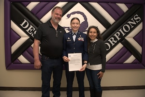 Air Force Junior ROTC Cadet Nicole Warner, a student at Desert Junior Senior High School on Edwards Air Force Base, Calif., poses with parents Aric Warner and Alma Warner during a brief ceremony in Desert JSHS, Feb. 10. Nicole, 17, was recently selected to receive a scholarship to attend an accredited aviation university participating in a private pilot license-training program in the summer of 2021.