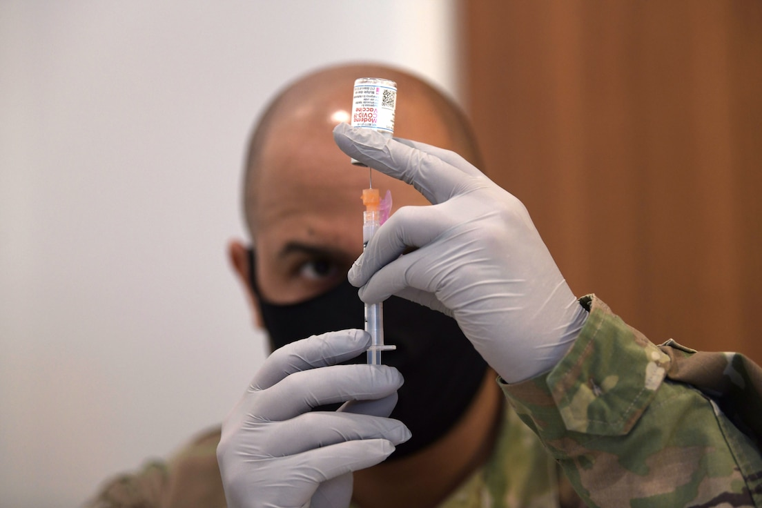Tech. Sgt. Defabian Johnson, a pharmacy technician from the 18th Medical Support Squadron, fills a syringe with the Moderna COVID-19 vaccine in preparation for the receiving patient, Jan. 29, 2021, at Kadena Air Base, Japan. As part of the DoD strategy for prioritizing, distributing and administering the COVID-19 vaccine, those providing direct medical care and emergency services will be prioritized to receive the vaccine at units based in Japan, including Kadena AB. (U.S. Air Force photo by Airman 1st Class Rebeckah Medeiros)