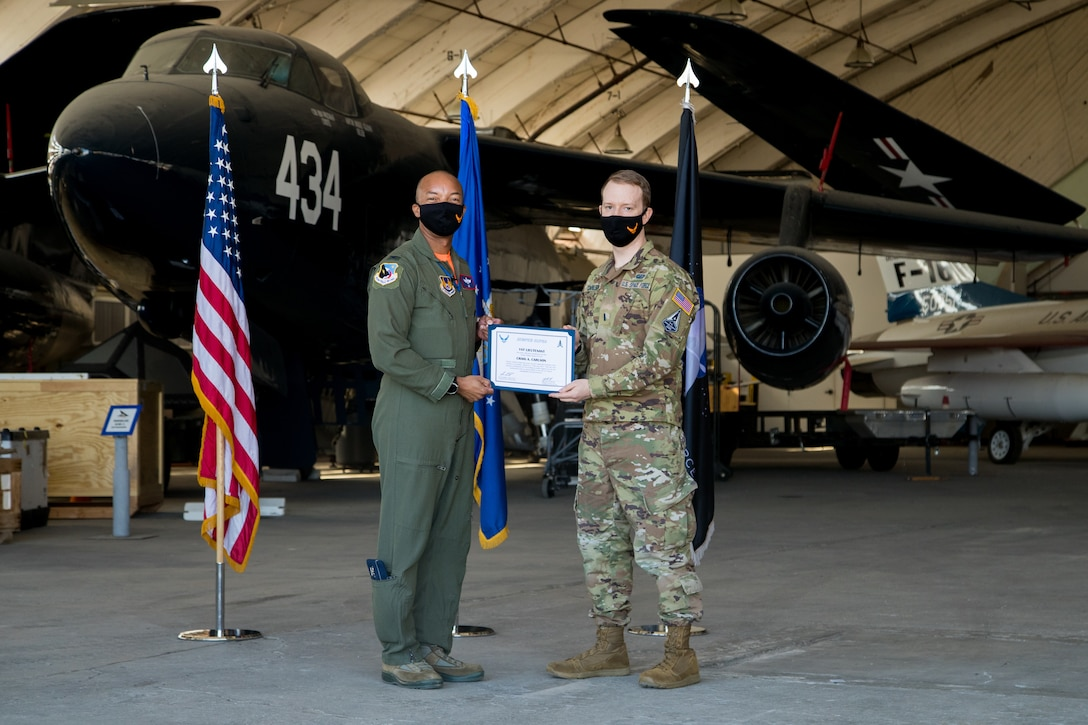 1st Lt. Craig Carlson, 412th Operations Group, originally of Boulder, Colorado, accepts his U.S. Space Force certificate from Col. Randel Gordon, 412th Test Wing Vice Commander during a Space Force Transfer Ceremony at Edwards Air Force Base, California, Feb. 11. (Air Force photo by Richard Gonzales)