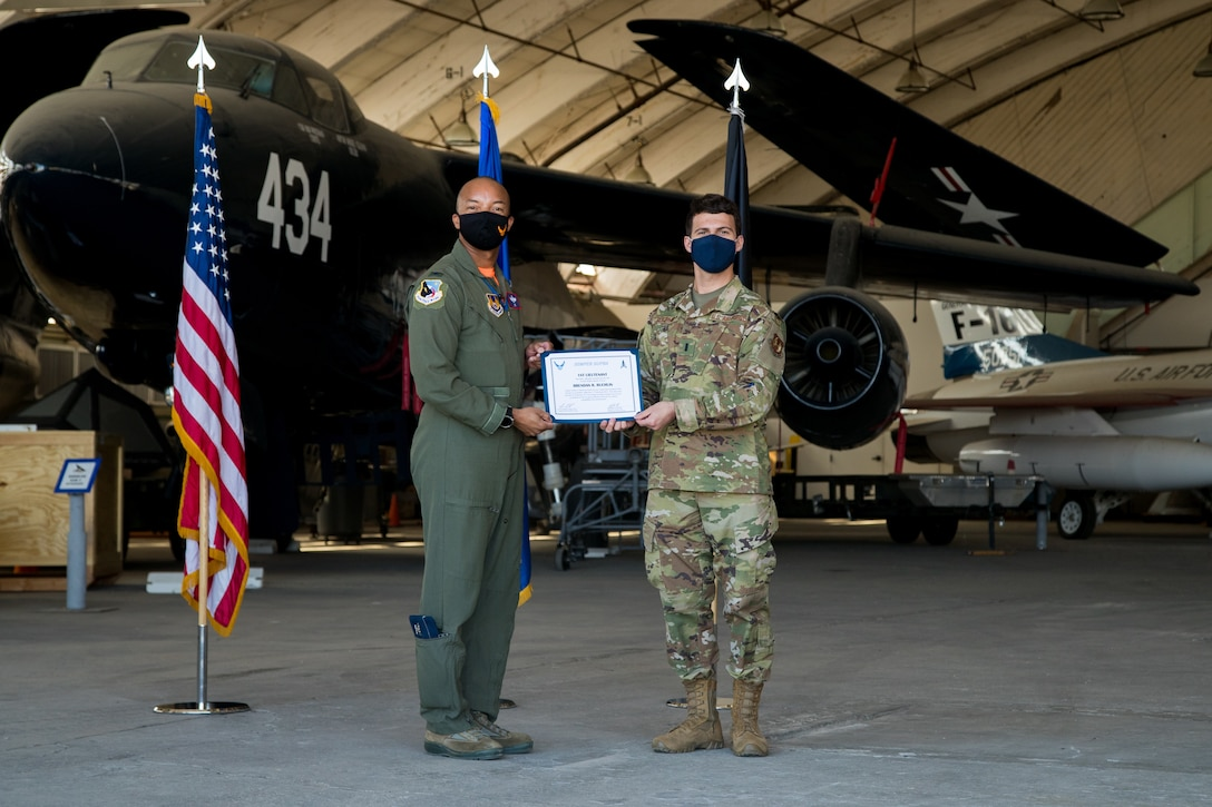 1st Lt. Brendan Ruchlin, 418th Flight Test Squadron, accepts his U.S. Space Force certificate from Col. Randel Gordon, 412th Test Wing Vice Commander, during a Space Force Transfer Ceremony at Edwards Air Force Base, California, Feb. 11. (Air Force photo by Richard Gonzales)