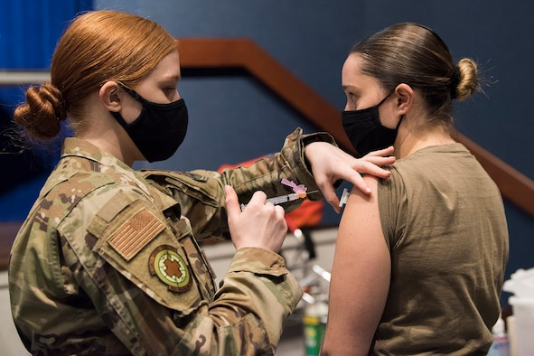 Airman 1st Class Dallas Telle (right), a client systems technician at the 709th Cyberspace Squadron at Patrick Space Force Base, Fla., rolls up her sleeve as Staff Sgt. Kameri Michaud (left), noncommissioned officer in charge of the 45th Medical Group's Pediatrics Clinic, administers the COVID-19 vaccine.  As a member of the Air Force Technical Applications Center's contingency response team, Telle received her first dose Jan. 14 and her second dose Feb. 11.  (U.S. Air Force photo by Matthew S. Jurgens)