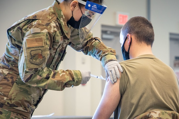 Staff Sgt. Bruna Souza, 102nd Medical Group, administers a COVID-19 vaccine during an immunization clinic at Otis Air National Guard Base, Feb. 6, 2021. The vaccine will be delivered in a phased approach, beginning with emergency services personnel, security forces, and medical and health care professionals.