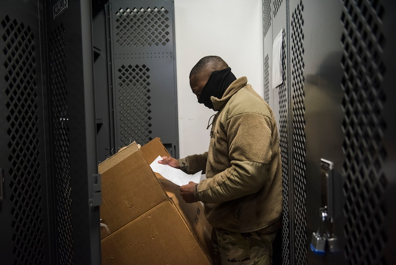 Man in uniform looking at supply equipment in storage facility
