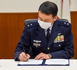Japan Air Self-Defense Force Maj. Gen. Takahiro Kubota, 3rd Air Wing commander, signs the Memorandum of Understanding 3010 at Misawa Air Base, Japan, Feb. 12, 2021. The MOUI, which is the first of its kind to be signed in more than 20 years at Misawa, covers a variety of areas including the use and maintenance of roadways and airfield pavements, and the possible installation of buildings, structures, utility systems or other real property built separately or apart from existing structures. (U.S. Air Force photo by Tech. Sgt. Timothy Moore)
