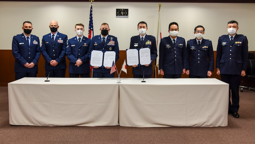 U.S. Air Force and Japan Air Self-Defense Force members pose for a photo with signed copies of the Memorandum of Understanding International 3010 at Misawa Air Base, Japan, Feb. 12, 2021. The first of its kind to be signed in more than 20 years at Misawa, MOUI 3010 outlines the responsibilities associated with the joint or sole use, maintenance, repair, and construction of U.S. and Japanese owned facilities and areas on Misawa Air Base. (U.S. Air Force photo by Tech. Sgt. Timothy Moore)