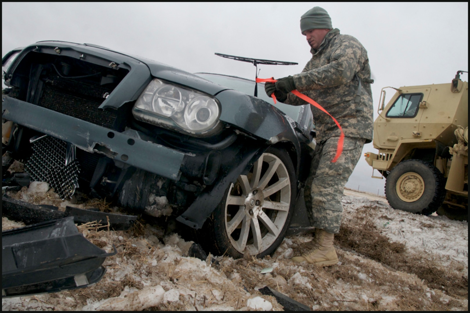 Sgt. Joseph English, of Newalla, Oklahoma, ties a fluorescent ribbon to a wrecked car, marking it as searched and clear of passengers while he and other Soldiers patrolled a section of Interstate 35 north of Perry, Okla., Dec. 28, 2015.