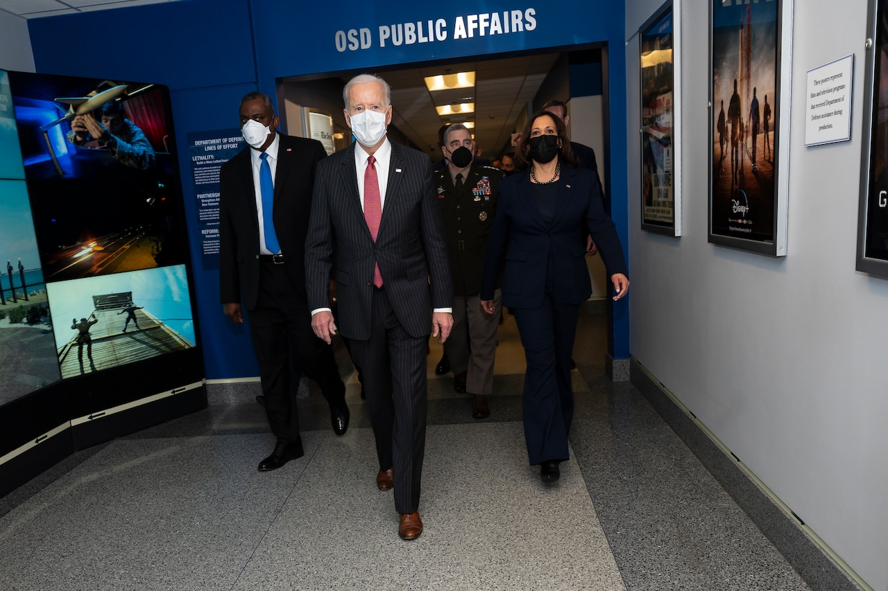 President Joe Biden and Vice President Kamala Harris walk down a hallway in the Pentagon with other leaders.