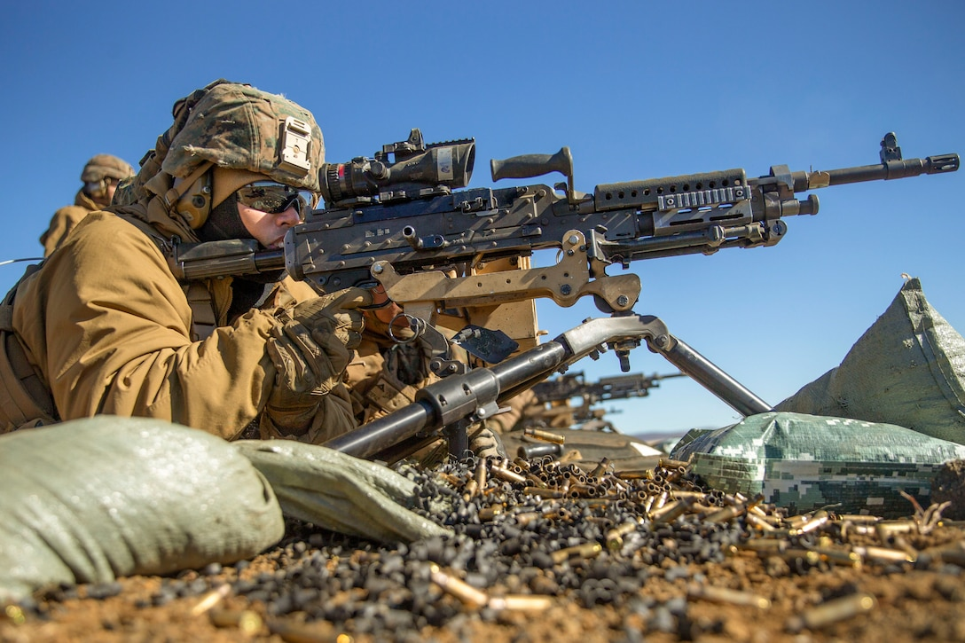 A sailor aims a weapon while lying on the ground.