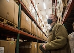 Man in uniform looking at boxes in a warehouse