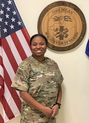 """Kentucky National Guard Maj. Mitisha Martin Aug. 20, 2020, in Poland with the 1163rd Area Support Medical Company's motto: """"Whatever it takes."""""""