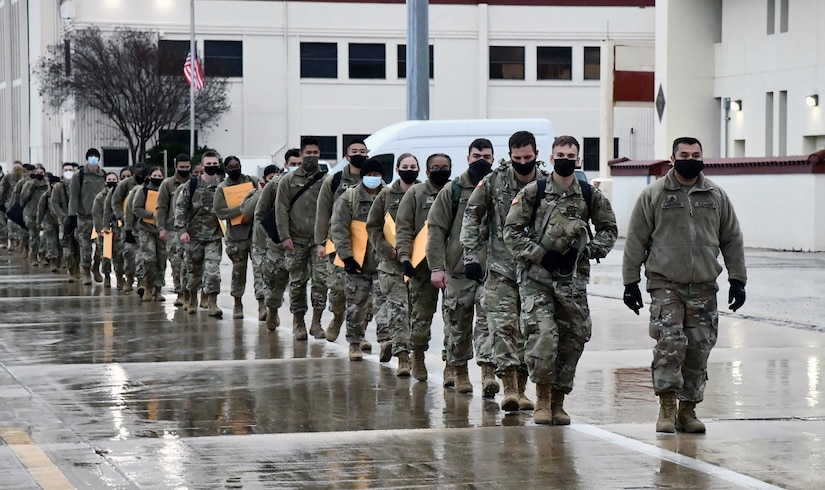 U.S. Army Medical Center of Excellence Advanced Individual Training Soldiers walk in formation at Joint Base San Antonio-Kelly Field Annex before boarding a contract airplane that will take them to their first duty assignment.