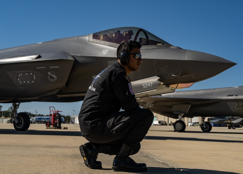 An Air Force maintainer kneels in front of an F-35