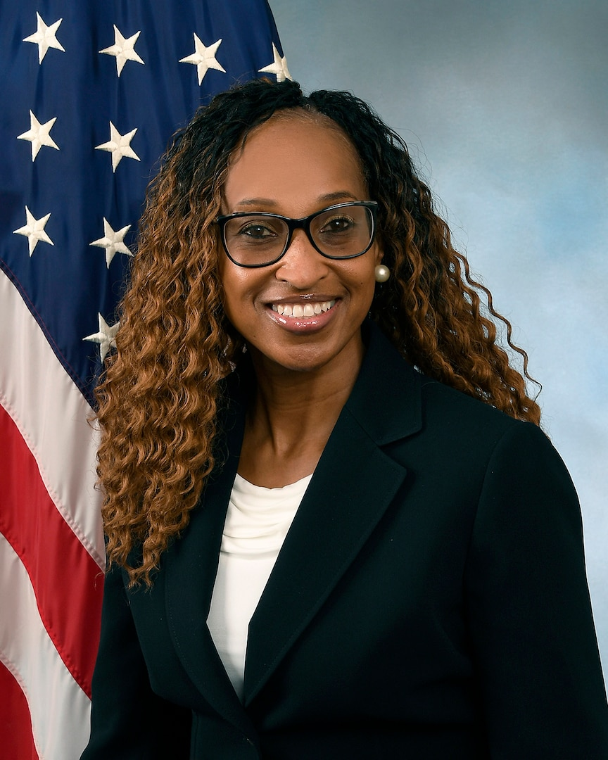 Sabrina in a black suit jacket with a white shirt in front of the flag and blue background.