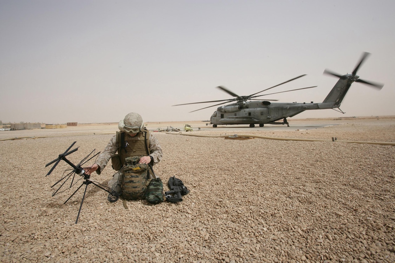 A service member keels on a bed of rocks to work on a satellite communications device; a helicopter is in the background.