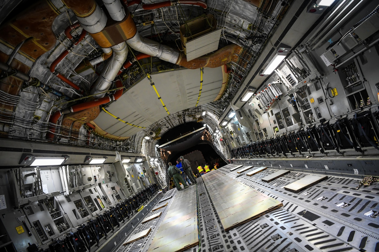 Airmen stand inside the cargo bay of an aircraft.