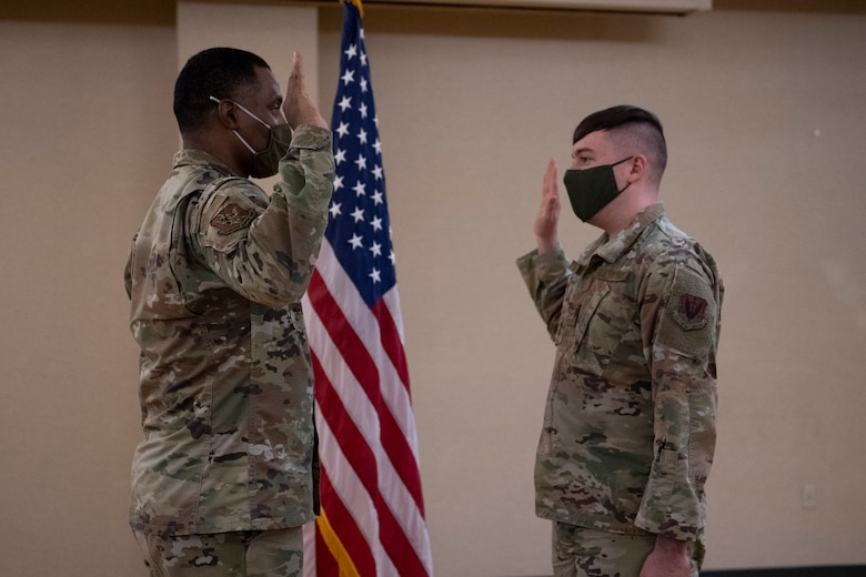 A photo of two Airmen raising their right hands during an enlistment.