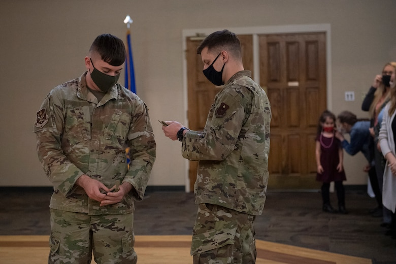A photo of an Airman putting a patch on another Airman's uniform.