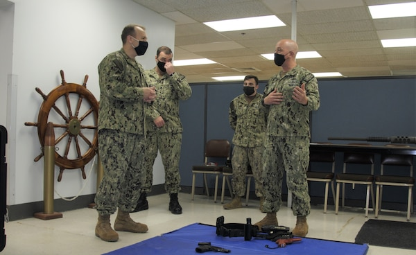 Rear Adm. Tom Anderson, Program Executive Officer, Ships, reviews the Firearms Training System (FATS), a new simulated use of force option that Sailors can use to fulfill their weapons qualifications training.