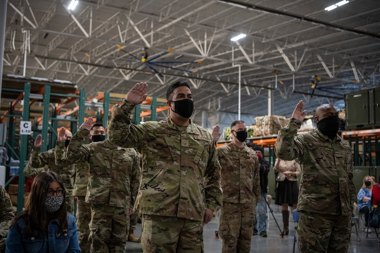 Men and Women take the oath of Enlistment at a ceremony.
