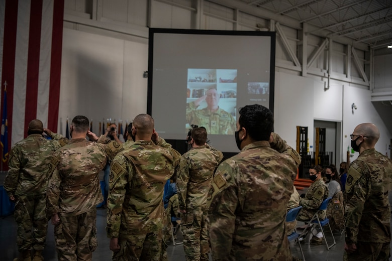 Men and Women salute a Colonel that is broadcasting in from a zoom call.