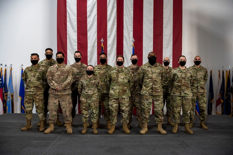 Men and women stand together for a group photo wearing masks.