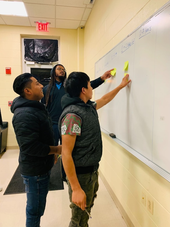 Students point to a marker board.