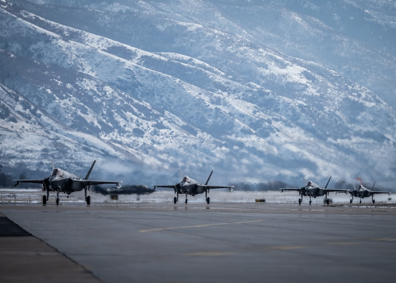 F-35s on a flightline with mountains in the background