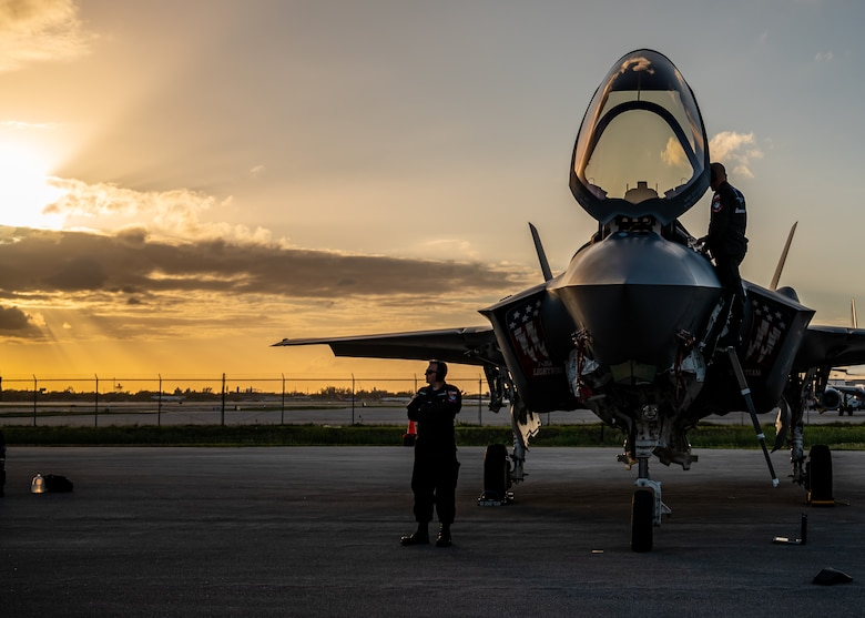 Maintainers work on an F-35 while the sun sets.