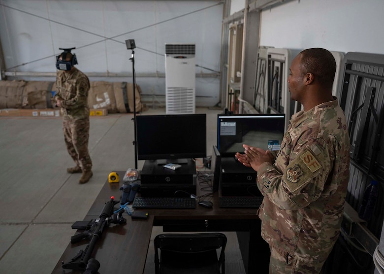 U.S. Air Force Tech. Sgt. Frank Unsioug (left), 380th Expeditionary Security Forces Squadron (ESFS) combat arms instructor, uses a virtual reality (VR) system in a virtual response as Master Sgt. Kenneth Greene (right), 380th ESFS training NCO in charge, analyzes his performance at Al Dhafra Air Base, United Arab Emirates, Jan. 20, 2020.