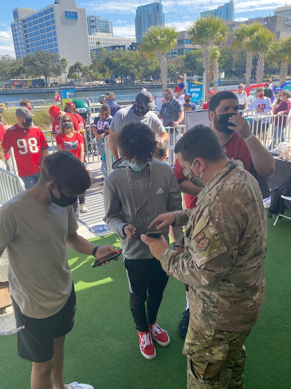 Tech. Sgt. Jonathan Bell, a special warfare recruiter with the 330th Recruiting Squadron, showed a group of fans the airforce.com webpage while waiting to use the AIR RAID QB SIM Experience.