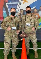 Master Sgt. Daniel Bedford, Air Force Recruiting Service national events program manager, and Chief Master Sgt. Antonio Goldstrom, AFRS command chief, pose for a photo at the AIR RAID QB SIM Experience at the Super Bowl LV Experience outside of Raymond James Stadium in Tampa, Florida, Jan. 31, 2021
