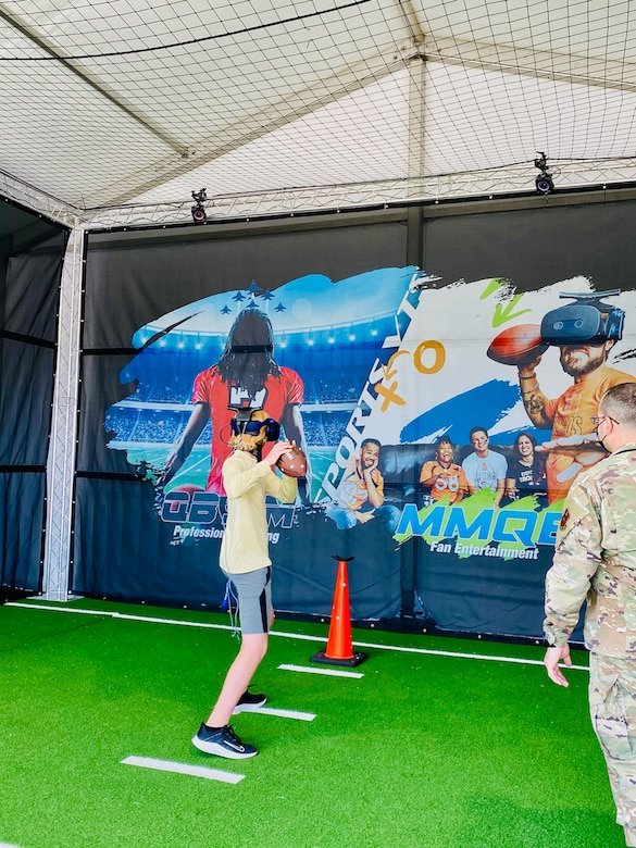 A young fan prepared to throw the football while using the Air Force's AIR RAID QB SIM Experience at the Super Bowl LV experience outside of Raymond James Stadium in Tampa, Florida, Jan. 31, 2021.
