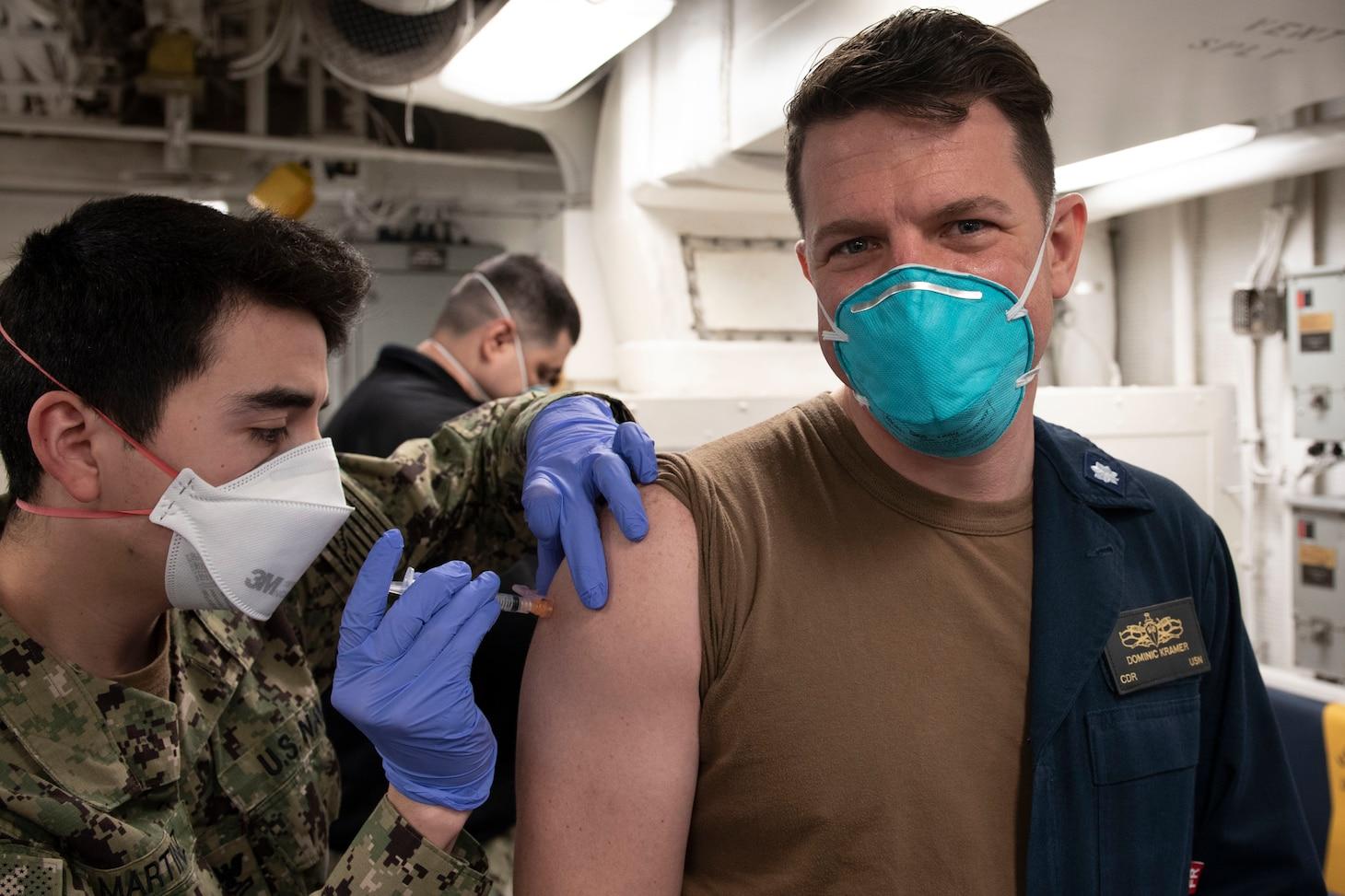 Sailors receive the COVID-19 vaccine aboard USS Mitscher (DDG 57).