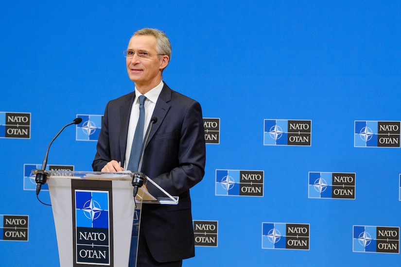 A civilian speaks at a lectern.