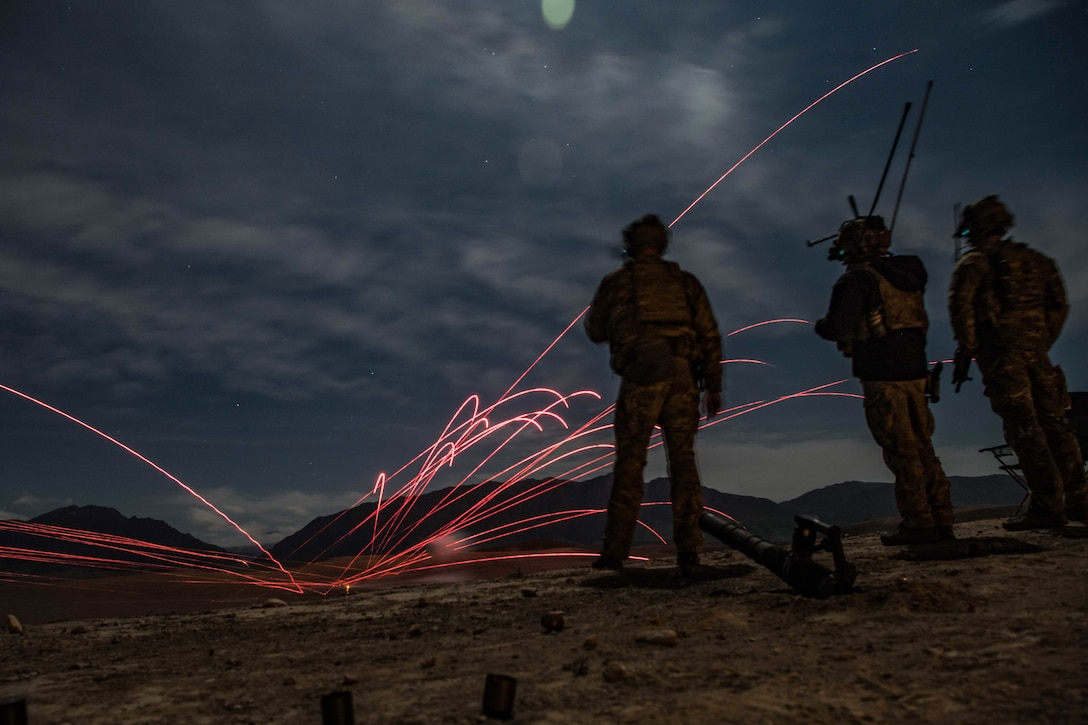 Tracers skim through the sky as service members look on in Afghanistan.