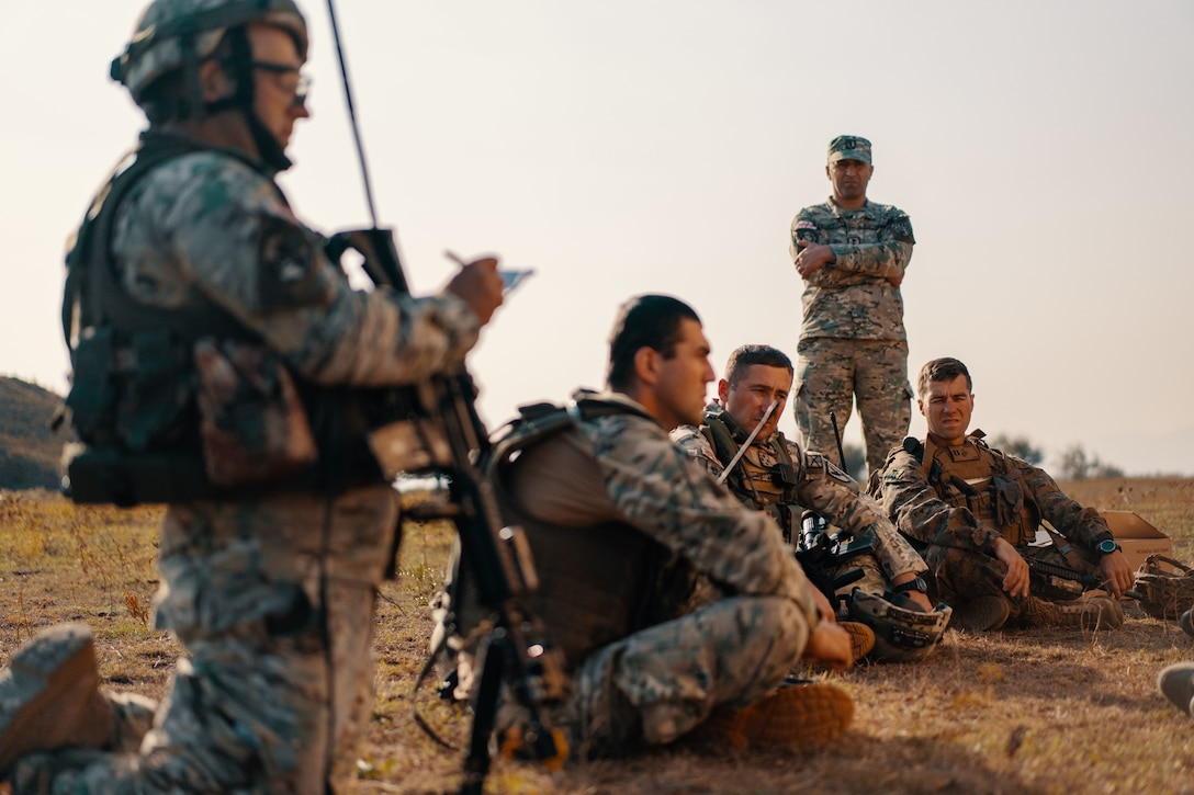 Foreign soldiers discuss a mission.