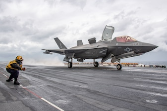 Aviation Boatswain's Mate (Handling) 2nd Class Cosme Zamora, from Compton, Calif., assigned to amphibious assault ship USS America (LHA 6), launches an F-35B Lightning II fighter aircraft assigned to the 31st Marine Expeditionary Unit (MEU) from the ship's flight deck.
