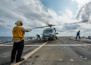 "Boatswain's Mate 1st Class Eric Irish, from Queensbury, N.Y., directs Sailors away from an MH-60S Sea Hawk, assigned to the ""Eightballers"" of Helicopter Sea Combat Squadron (HSC) 8, on the flight deck of the Arleigh Burke-class guided-missile destroyer USS John Finn (DDG 113)."