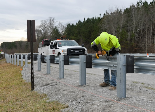 Ben Dees secures a section of guardrail while working on a crew installing new guardrails along Wattendorf Memorial Highway at Arnold Air Force Base, Tenn., Jan. 27, 2021. Guardrails were added to areas where the shoulder drops off and at bridge ends to increase safety for motorists. (U.S. Air Force photo by Jill Pickett)