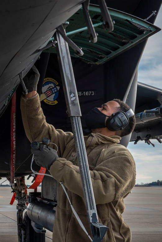 Senior Airman Thiago Santos, 4th Fighter Readiness Squadron electronics technician, attaches a test harness onto an F-15E Strike Eagle at Seymour Johnson Air Force Base, North Carolina, Feb. 3, 2021.
